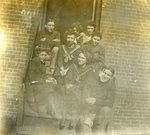 LU-083.1753 - Unknown group of men and women seated on doorstep. Circa early 1900s