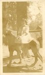 HS-022.006, Unidentified young girl sitting on dog statue