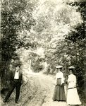 LU-157.0043 - Dr. Elmer Jones, Miss Hill, and Miss London with bows & arrows on road through woods by John Chester Mattoon