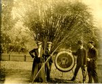 LU-157.0045 - unknown woman, John C. Mattoon (left of target), unknown man, and Dr. Elmer Jones (far right) with archery target by John Chester Mattoon