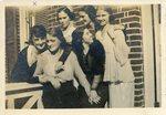 LU-387.020, Six unidentified women standing outside unidentified campus building. by Katherine Krebs